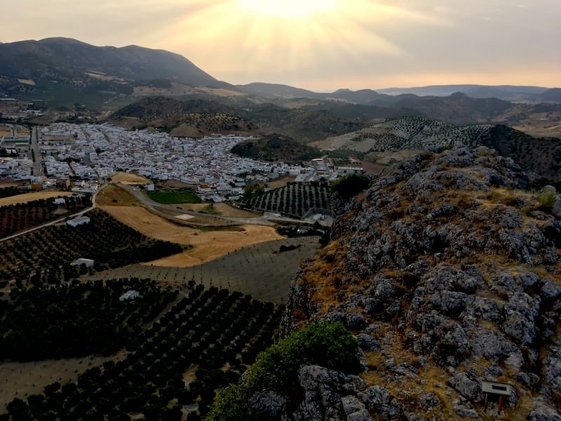 View from the top of Castillo De Hierro looking out to white Spanish towns and mountains at sunrise