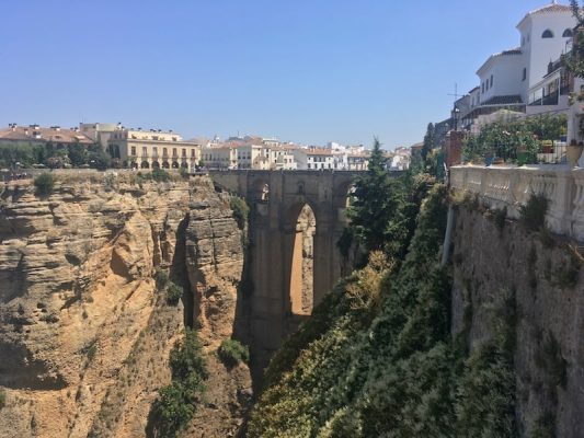 Spanish town of Ronda high on the cliffs, showing the bridge that traverses a 120m gorge joint the new & old parts of town.